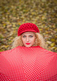 Attraktives blondes Mädchen mit der roten Kappe, die über Trieb des roten Regenschirmes im Freien schaut. Attraktive junge Frau in Stockfoto