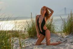 Attraktives blondes Mädchen mit perfektem dünnem Körper im schwarzen sexy Badeanzug, der auf dem Strand aufwirft Lizenzfreie Stockfotos