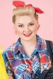 Attraktives blondes Mädchen mit Stift-obenmake-up Schönes Lächeln von Blondinen mit rotem Schal auf Kopf auf Pastellrosahintergru stockbilder