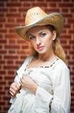 Attraktives blondes Mädchen mit Strohhut und weißer Bluse Stockfotografie