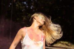 Attraktives blondes Mädchen mit Wind im Haar, das an Holi-Festival aufwirft Lizenzfreie Stockbilder