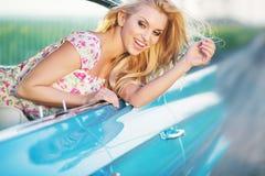 Attraktives blondes Mädchen, welches das blaue Cadillac reitet Lizenzfreie Stockbilder
