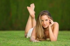 Attraktives blondes Mädchen, welches das Lügen auf dem Rasen in einem Park aufwirft Stockbild