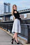 Attraktives blondes Mode-Modell, das recht auf dem Pier mit Manhattan-Brücke auf dem Hintergrund aufwirft Stockfoto
