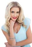 Attraktives blondes Modell im blauen Kleid, das Kamera betrachtet stockbild