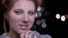 Attraktives blondes Modell mit dem hellen Make-up, das modern ihr Gesicht auf unscharfem Lichthintergrund aufwirft und berührt stock footage