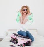 Attraktives blondes Versuchen, ihren Koffer zu schließen Lizenzfreie Stockfotos