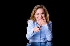 Attraktives blondes weibliches Lachen und Punkt vorwärts Stockfotos