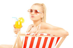 Attraktives blondes weibliches Sitzen auf einem Sonnenruhesessel und einem trinkenden a Stockfoto