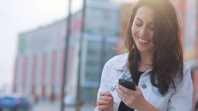 Attraktives braunhaariges kaukasisches Mädchen, das in der Sonne vor Einkaufszentrum bleibt und ihren Smartphone, herein schauend stock video
