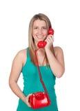 Attraktives Brunettemädchen, das mit rotem Telefon nennt Stockbild