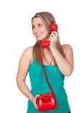 Attraktives Brunettemädchen, das mit rotem Telefon nennt Lizenzfreie Stockbilder