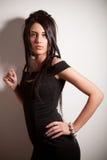 Attraktives Brunettemädchen im Art und Weiseschwarzkleid Stockfotos