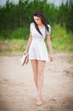 Attraktives Brunettemädchen mit kurzem weißem Kleid barfuß schlendernd auf die Landschaftsstraße Junges schönes Frauengehen Lizenzfreies Stockfoto