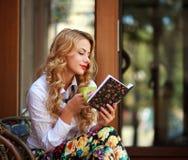 Attraktives Buch der jungen Frau Lesebeim Trinken des Kaffees stockfotos