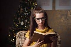 Attraktives Buch der jungen Frau Lesenahe Weihnachtsbaum lizenzfreie stockfotografie