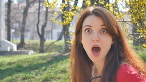 Attraktives emotionales junges Mädchen im roten Hemd beseitigt Sonnenbrille und betrachtet die Kamera mit Überraschungsausgabe stock video footage