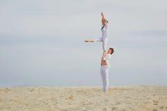 Attraktives erwachsenes Paar balanciert, Acroyoga tuend Stockbild