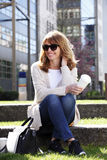 Attraktives Frauensitzen im Freien Lizenzfreies Stockbild