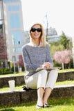 Attraktives Frauensitzen im Freien Stockfoto