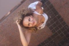 Attraktives gelocktes blondes Mädchen, das auf der Straße und dem Schauen steht Stockfoto