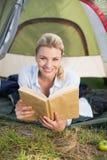 Attraktives glückliches blondes Lügen im Zelt, das Buch hält Stockbilder