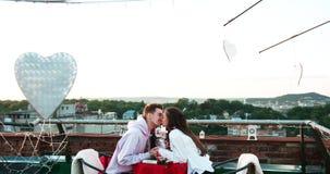 Attraktives glückliches junges Paarhändchenhalten und weich Reibungsnasen während des Datums am Dach verziert mit Metall stock footage
