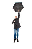 Attraktives hübsches Fliegen des jungen Mannes mit Regenschirm Lizenzfreies Stockfoto