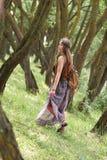 Attraktives Hippiemädchen, das unter den Bäumen im Wald geht lizenzfreies stockfoto