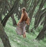 Attraktives Hippiem?dchen, das unter den B?umen im Wald geht stockbild