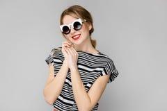 Attraktives junges überzeugtes blondes Mädchen in gestreifter Bluse lächelnd in der Sonnenbrille auf grauem Hintergrund Stockfotos
