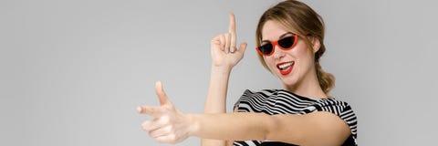 Attraktives junges blondes Mädchen in gestreifter Bluse lächelnd in der Sonnenbrille, welche die Stellung auf grauem Hintergrund  lizenzfreies stockfoto