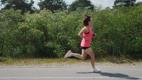 Attraktives junges brunette Mädchen im rosa Hemd, das durch Park läuft Sportive Frau, die Übungen tut Mädchen in den Kopfhörern h stock video