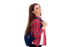 Attraktives junges Brunettestudentenmädchen mit dem blauen Rucksack lokalisiert auf weißem Hintergrund Stockfotografie