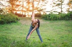Attraktives junges Eignungsfrauentraining im Park sie macht a Lizenzfreies Stockbild