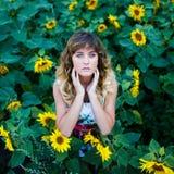Attraktives junges Mädchen auf dem Gebiet von Sonnenblumen stockfoto