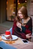 Attraktives junges Mädchen, das in einem Café sich versteckt hinter einer warmen Decke sitzt draußen Im Herbst Die Küken wuchsen  stockfoto