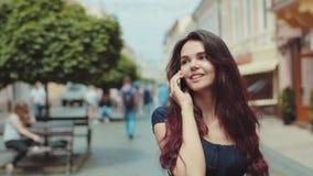 Attraktives junges Mädchen geht hinunter die gedrängte Stadtstraße, aufhebt das Telefon, spricht glücklich Shops, Passanten, städ stock footage
