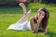 Attraktives junges Mädchen mit dem Gänseblümchen, das auf Gras liegt lizenzfreie stockfotos