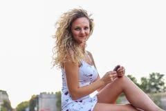 Attraktives junges Mädchen mit dem gelockten blonden Haar, das betrachtet, kam Stockbilder