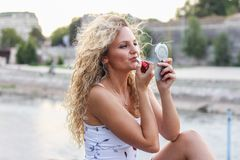 Attraktives junges Mädchen mit dem gelockten blonden Haar, das einen Lippenstift setzt Stockfotos