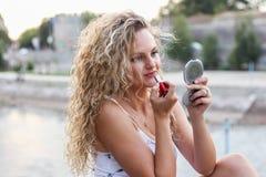 Attraktives junges Mädchen mit dem gelockten blonden Haar, das einen Lippenstift setzt Stockbild