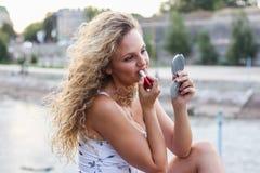 Attraktives junges Mädchen mit dem gelockten blonden Haar, das einen Lippenstift setzt Stockfoto