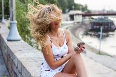 Attraktives junges Mädchen mit dem gelockten blonden Haar, das versucht, ihr M zu regeln Stockfotos