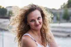 Attraktives junges Mädchen mit dem gelockten blonden Haar lächelnd und schauend Stockfotos