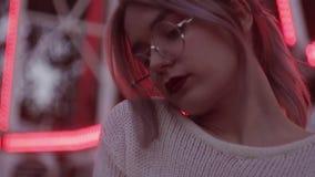 Attraktives junges Mädchen mit dem Pferdeschwanz in den runden Gläsern an amusment Park stock video footage