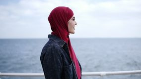 Attraktives junges Mädchen mit hijab auf ihrem Kopf geht angenommen nahe der Seeseite mit den Seemöwen, die auf fliegen stock footage