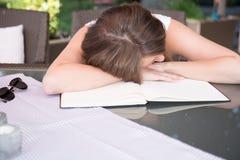 Attraktives junges Mädchen schläft auf Arbeitsbuch Stockfotografie