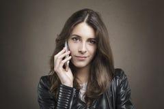 Attraktives junges Mädchen am Telefon, das Kamera auf Beschaffenheitsrückseite betrachtet Stockbilder