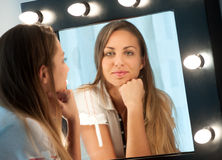 Attraktives junges Mädchen, das in den Spiegel anstarrt Stockbild